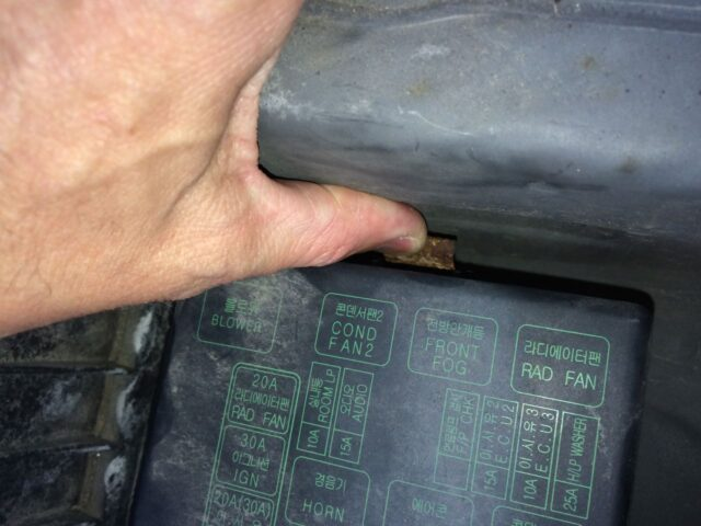 Prying away the top fuse box lid tab