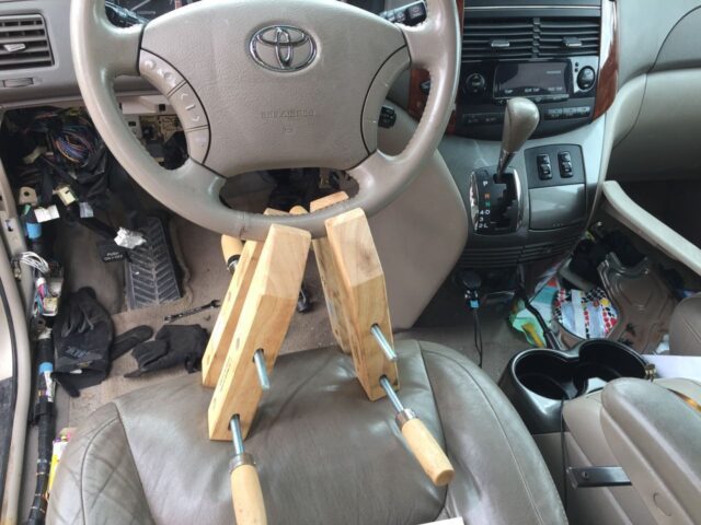 Using wood clamps, wedged against the seat, to hold the steering wheel straight