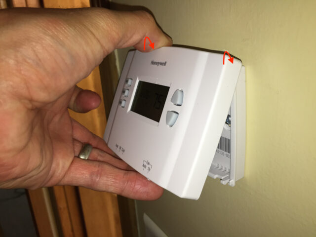 Hooking the top of the thermostat onto the mounting plate