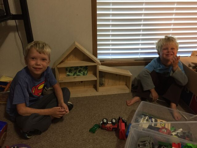 Boys posing with the doll house.