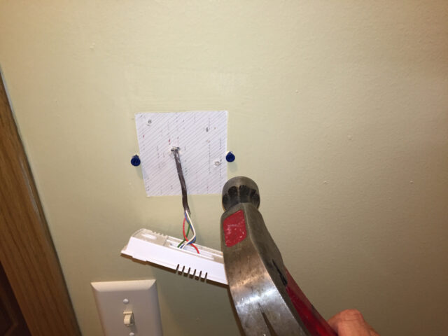 Tapping the anchors into the wall with a hammer