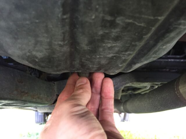 Unscrewing the drain plug by hand